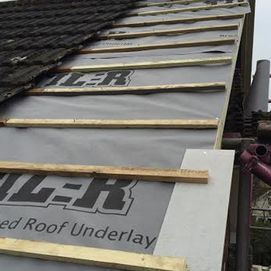 replacing old roof tiles with new ones